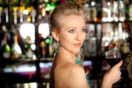 night club interior: Young beautiful blonde woman with a glass of wine standing at a bar counter