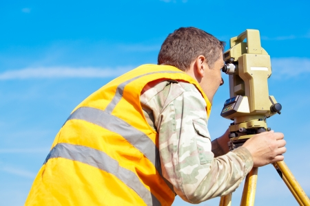 Inżynier geodeta dokonywania pomiaru z optycznym teodolit sprzęt na tle niebieskiego nieba