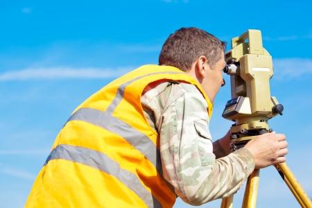 teodolito: Ingeniero topógrafo haciendo de medición con teodolito de equipos ópticos en el cielo azul de fondo