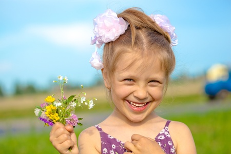 Happy smiling girl with flowers having fun outdoors Stock Photo