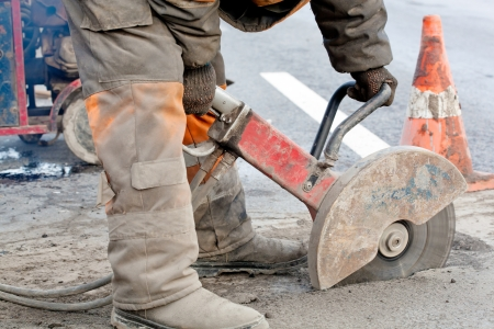 Cutting asphalt road for repair by hydraulic driven angle grinder; road works; upgrading road surfaces; horizontal orientation