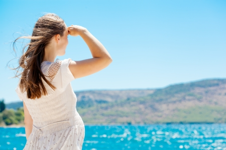 Young pregnant woman with her hair in summer dress standing by blue sea and looking into the distance