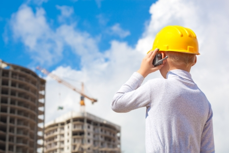introduces: Boy in a helmet and with toy portable radio introduces himself construction worker Stock Photo