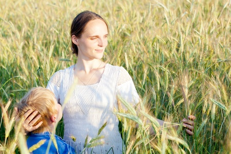 Young woman with her child in field of wheat; son looking up at mom photo