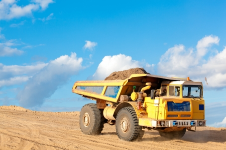 Heavy dump truck unloads soil on the sand at a construction site photo