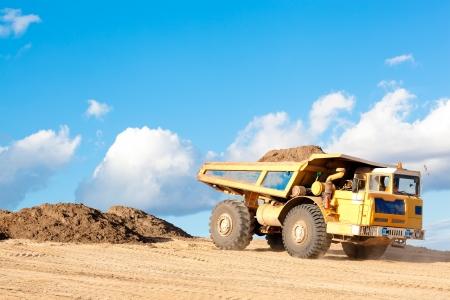 camion volquete: Vuelca cami�n con arena o tierra en un cuerpo en una obra de construcci�n