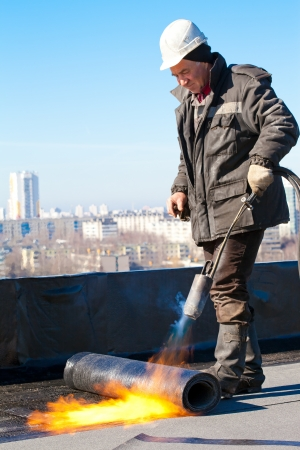 Dakdekker man arbeider in helm installeren van een rol dakleer door middel van gas blaaspijp toorts