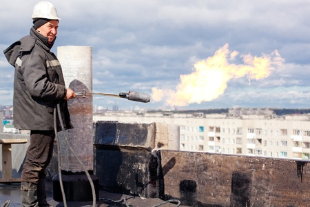 Positive roofer workman in uniform with a gas torch during roofing works Stock Photo - 15376242