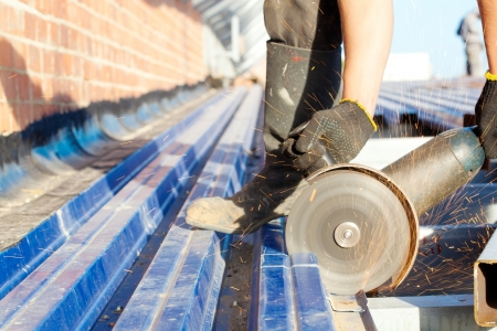 Construction worker sawing steel sheet with trapezoidal profile during roofing works Stock Photo