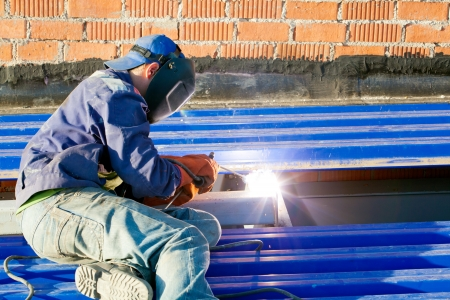 Industrial worker welder in workwear and mask during roofing works by means of inverter welding machine