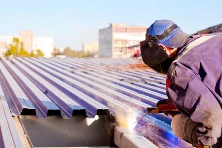 Welder worker in uniform and mask during roofing works by means of inverter welding machine Standard-Bild