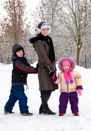 Family of mother and children relaxing at snow in winter photo