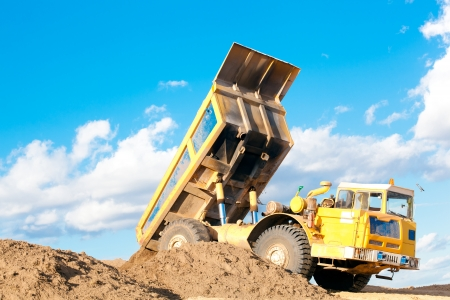 Lourd camion à benne décharge du sol sur le sable sur un chantier Banque d'images