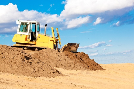 Bulldozer machine moving soil at construction site during earth moving works Stock Photo
