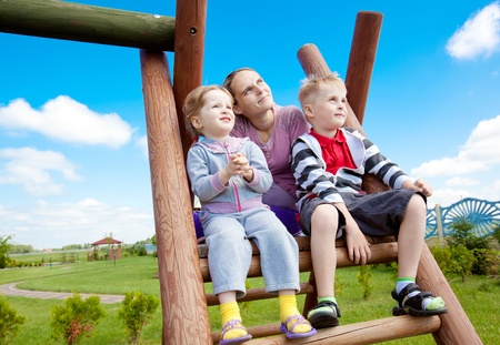 Happy family of mother and children looking up into the distance at park playground Stock Photo