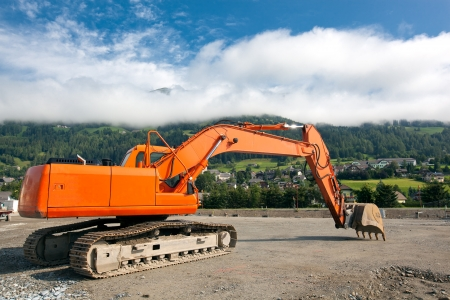 Excavator with metal tracks at construction site on austrian alps background photo