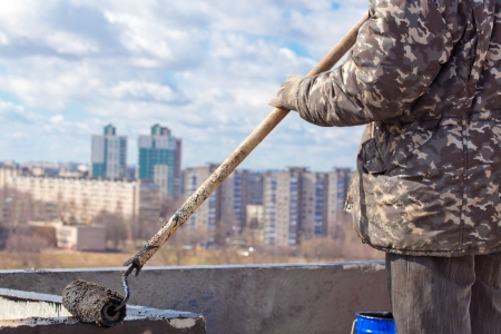 tar felt: Roofer worker painting black coal tar or bitumen at concrete surface by the roller brush; creating waterproofing barrier Stock Photo