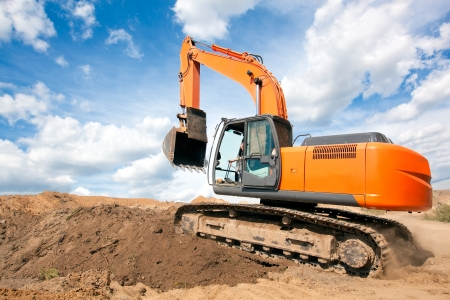 'earth mover': Excavator machine moves with raised bucket on construction site during earth moving works Stock Photo