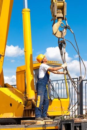 camion grua: Trabajador de la construcción en marcha uniforme y de protección durante las obras de elevación de grúa móvil