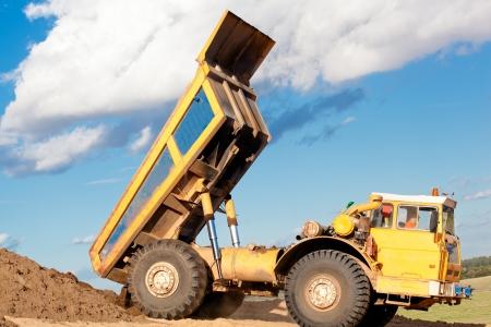 mining truck: Camión volquete pesado descarga suelo en la arena en una obra en construcción
