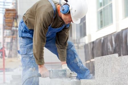 grind: Trabajador industrial hace un corte horizontal con una mano sierra el�ctrica durante alinear las baldosas de m�rmol