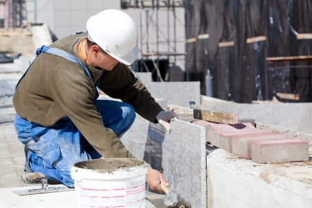 Tiler in helmet and work wear installing marble tiles at construction site