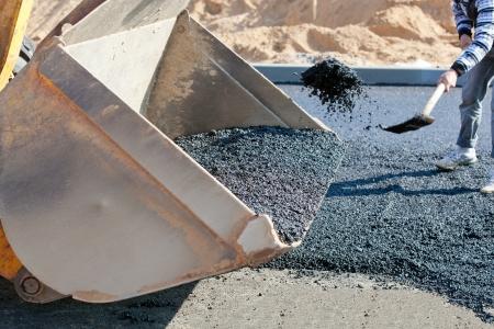 blacktopping: Asphalt in a wheel loader bucket during roadworks