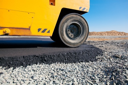 Road roller leveling fresh asphalt pavement during road construction and repairing works Stock Photo - 17696172