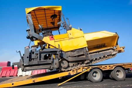 Transportation tracked paver machine during roadworks for asphalt paving