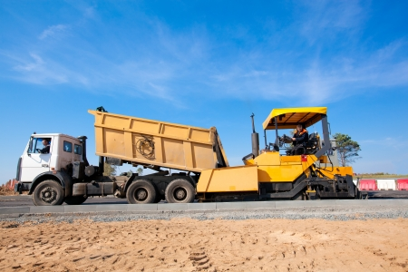 Tipper unloading fresh asphalt from body into tracked paver during pavements construction works Standard-Bild