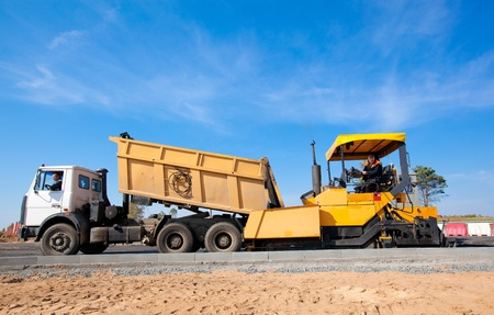 asphalt paving: Tipper unloading fresh asphalt from body into tracked paver during pavements construction works Stock Photo