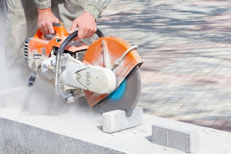 saws: Cutting and grinding concrete or metal using a cut-off saw Stock Photo