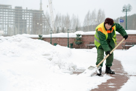 Woman worker in uniform shoveling snow after a storm