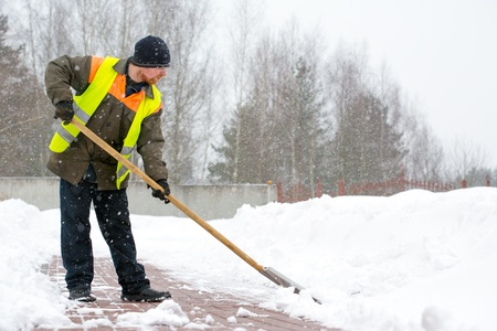 snow clearing: Man worker in uniform shoveling snow