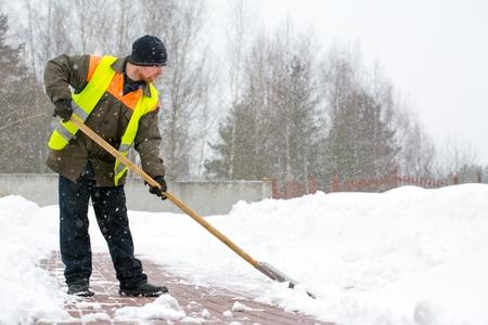 sidewalk: Man worker in uniform shoveling snow