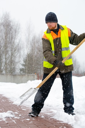 cold weather: Man worker in uniform shoveling snow