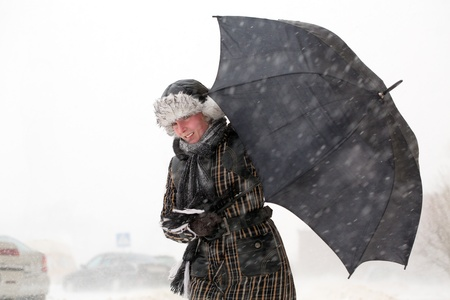 strong wind: Girl with umbrella during snow storm