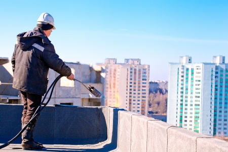 Roofer worker installing roofing felt by means of gas blowpipe torch