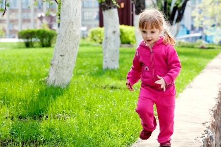 Small girl running on track Stock Photo