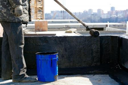 Dakwerker werknemer schilderen zwarte koolteer of bitumen op betonnen ondergrond door de roller kwast Stockfoto