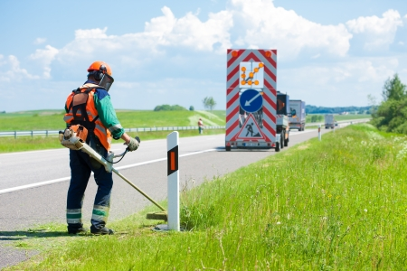 Road landscapers cutting grass around mileposts along the road using string lawn trimmer Stok Fotoğraf