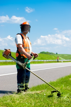Road landscapers cutting grass along the road using string lawn trimmers Stock Photo