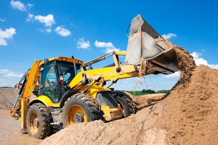 wheel loader: Excavator machine unloading sand with water during earth moving works at construction site