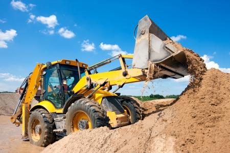 Macchina Escavatore scarico sabbia con l'acqua durante lavori di movimento terra in cantiere
