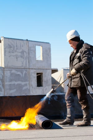 Roofer man worker in protective gear installing a roll of roofing felt by means of gas blowpipe torch