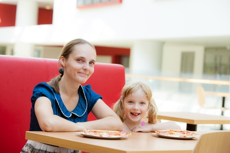 eating fast food: Family of mom and daughter relaxing in cafe
