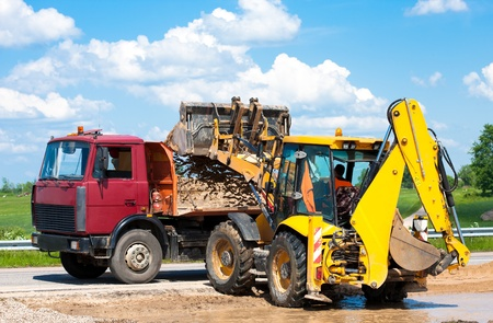 Wheel loader Excavator unloading sand into truck body during earthmoving works at construction site Stock Photo - 20872120