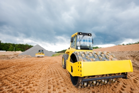 Soil compactor and bulldozer during road construction works