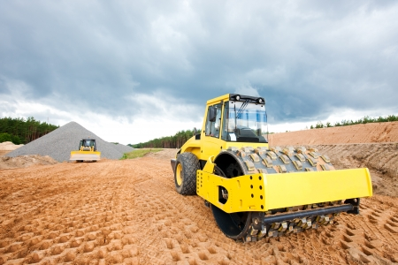 Soil compactor and bulldozer during road construction works photo
