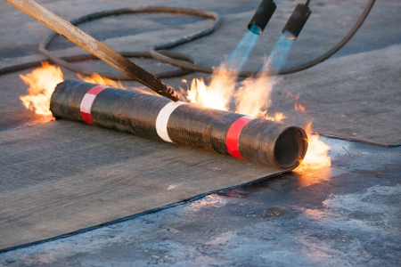 flat roof: Roll roofing Installation with propane blowtorch Stock Photo